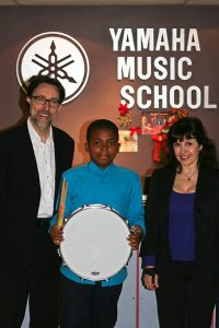 Jethro Paris receiving his new snare drum, drum stand, sticks and practice pad donated by Yamaha Canada at the Yamaha Music School in Toronto
