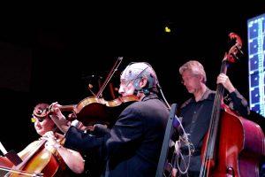 Up close is Ensemble Vivant's violist Norman Hathaway wearing brain signal sensor gear
