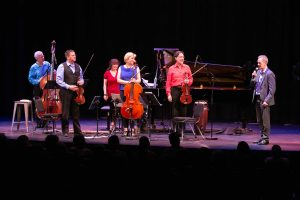 Ensemble Vivant L to R: Jim Vivian, bass, Corey Gemmell, violin; Catherine Wilson, piano; Sybil Shanahan, cello; Norman Hathaway, violin. Fredrik Alatalo, Chief Administrative Officer, telMAX with mic; standing ovations for Ensemble Vivant. Photo by Marion Voysey