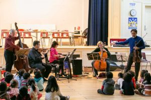 Ensemble Vivant performing for Kindergarten students; Norman Hathaway interacting with students