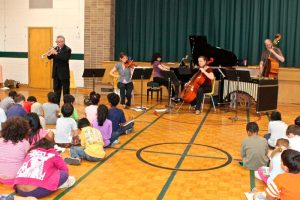 Ensemble Vivant performing for engaged students, many of whom are expressing their feelings about the music in descriptive drawings and words